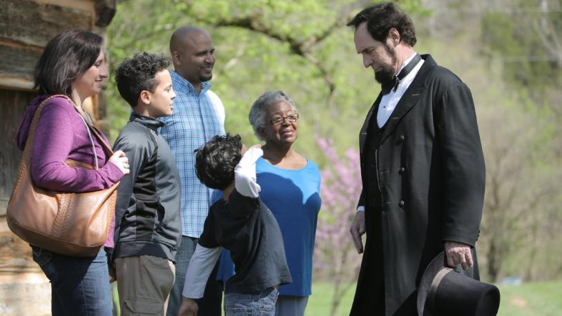 A multigenerational family interacts with a Lincoln impersonator at Abraham Lincoln Birthplace National Historical Park