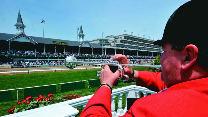 A bugler in a red jacket sounds the call at the Kentucky Derby, with the twin spires of Churchill Downs in the background