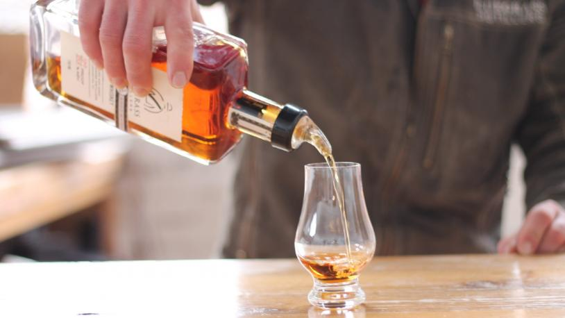 A bartender pours a tasting glass of bourbon at Bluegrass Distillers in Lexington