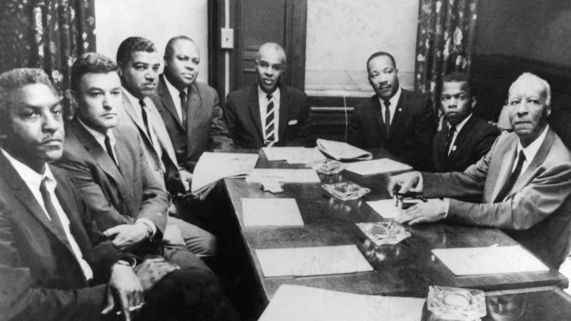 An archival photo of civil rights leaders around a table, including Whitney M. Young, Jr., and Dr. Martin Luther King, Jr.