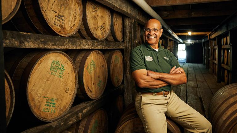 Freddie Johnson, a tour guide at Buffalo Trace Distillery in Frankfort, KY, sits in front of bourbon barrels in the rickhouse