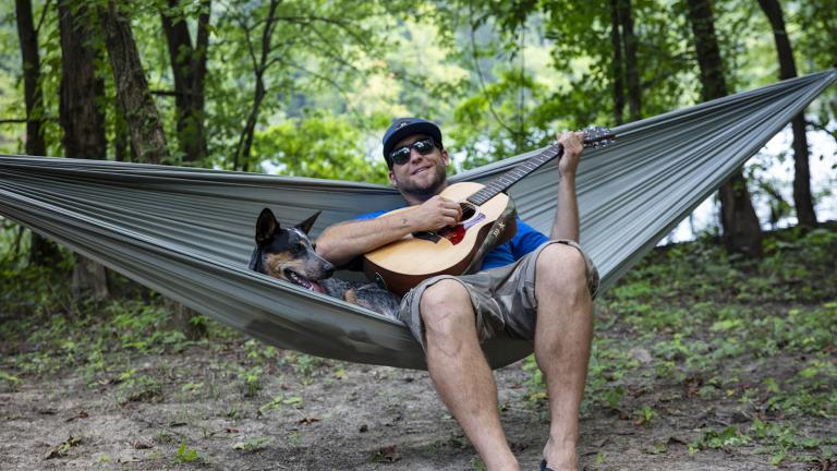 Host Adam Glick relaxes in a hammock with his dog